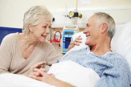 Senior Nő Látogató Férj kórházi ágyon Stock fotó