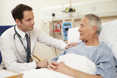 医者病院で男性患者のベッドのそばに座って