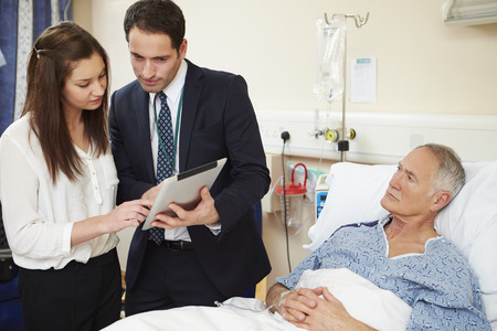 reassurance: Medical Staff On Rounds Standing By Male Patients Bed