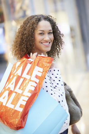 Excited Female Shopper With Sale Bags In Mall Stock Photo