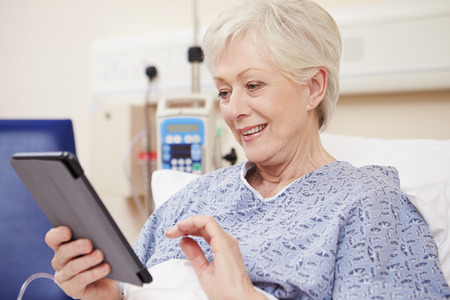 e book reader: Senior Female Patient Using Digital Tablet In Hospital Bed