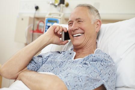 Старший пациент, используя мобильный телефон в больничной койке