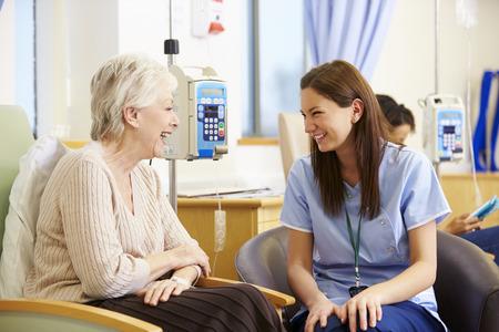 persona sentada: Mujer mayor que se someten a quimioterapia con la enfermera Foto de archivo