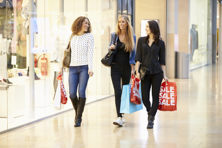 shopping center: Three Female Friends Shopping In Mall Together