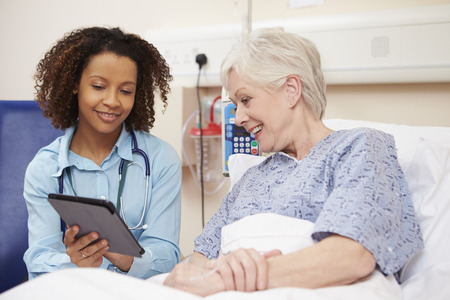 Doctor Sitting By Female Patient's Bed Using Digital Tablet Stockfoto