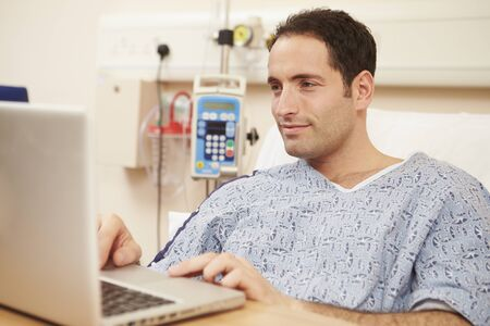 patient in hospital: Male Patient Using Laptop In Hospital Bed