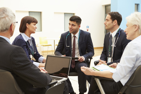 Group Of Consultants Sitting At Table In Hospital Meeting