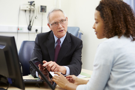 doctor's office: Doctor Showing Patient Test Results On Digital Tablet
