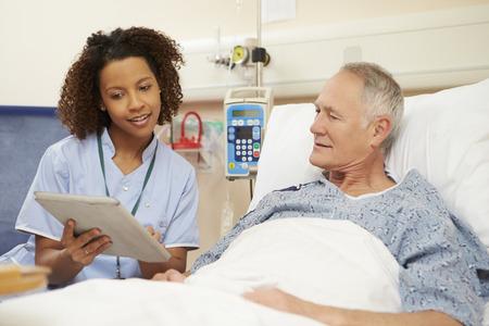 Nurse Sitting By Male Patient's Bed Using Digital Tablet Standard-Bild