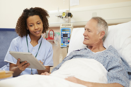 Nurse Sitting By Male Patient's Bed Using Digital Tablet Stockfoto