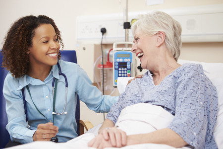 reassurance: Doctor Sitting By Female Patients Bed In Hospital