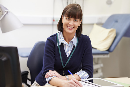 Portrait Of Female Consultant Working At Desk In Office