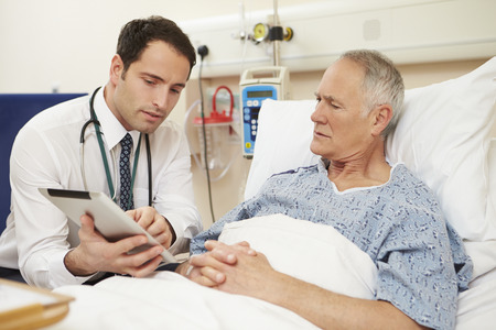 concerned: Doctor Sitting By Male Patients Bed Using Digital Tablet Stock Photo