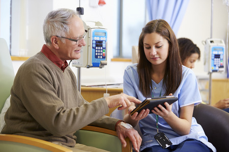 Man Having Chemotherapy With Nurse Using Digital Tablet Stock Photo