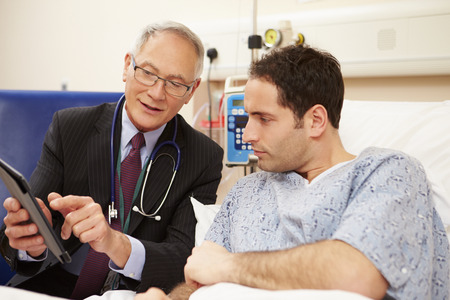 Doctor Sitting By Male Patients Bed Using Digital Tablet Stock fotó