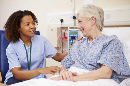 Nurse Sitting By Female Patient's Bed In Hospital Stockfoto