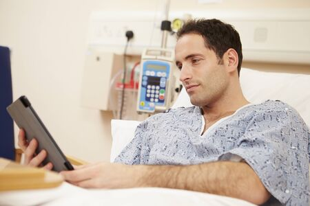 using tablet: Male Patient Using Digital Tablet In Hospital Bed