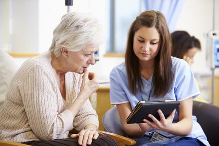 Mulher que tem a quimioterapia com enfermeira usa a tabuleta digital