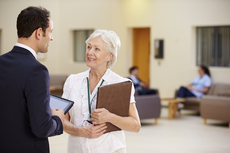 patient notes: Two Consultants Discussing Patient Notes In Hospital