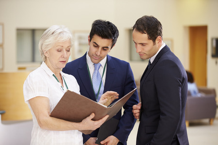 patient notes: Three Consultants Discussing Patient Notes In Hospital
