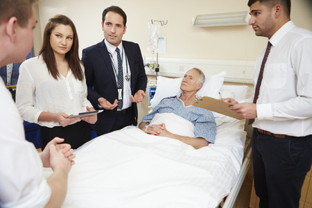rounds: Medical Staff On Rounds Standing By Male Patients Bed