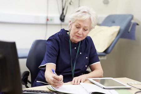 pielęgniarki: Kobieta Pielęgniarka biurku w pracy w biurze