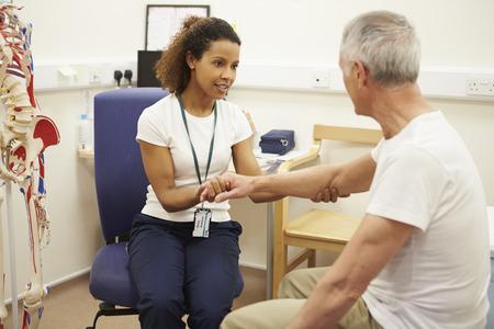 Старший пациент проходит курс физиотерапии в больнице Фото со стока