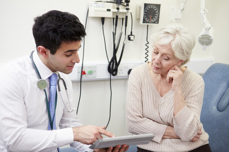 man doctor: Consultant Showing Patient Test Results On Digital Tablet