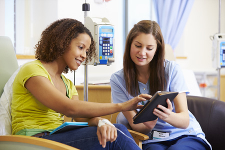 digital tablet: Woman Having Chemotherapy With Nurse Using Digital Tablet