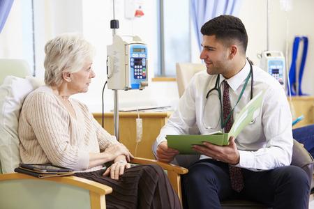 Mujer que tiene la quimioterapia con el médico mirando notas Foto de archivo