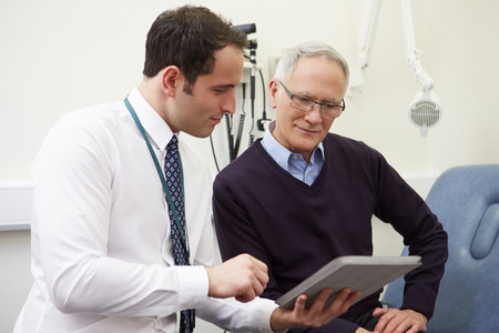doctor appointment: Consultant Showing Patient Test Results On Digital Tablet