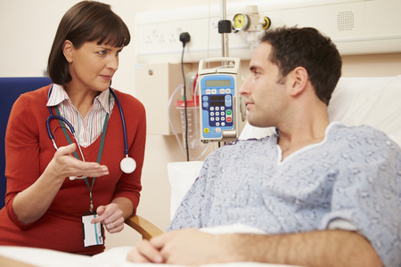 reassurance: Female Doctor Sitting By Male Patients Bed In Hospital