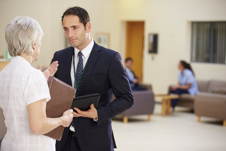 hospital patient: Two Consultants Discussing Patient Notes In Hospital