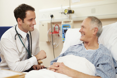 happy patient: Doctor Sitting By Male Patients Bed In Hospital