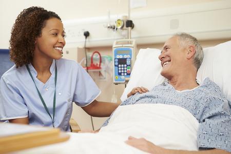 看護師病院で男性患者のベッドのそばに座って