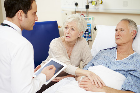 reassurance: Doctor With Digital Tablet Talking To Couple By Hospital Bed