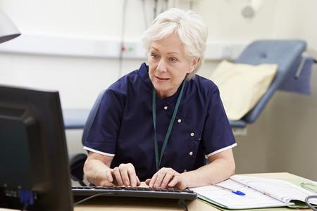 nurses: Enfermera Que Trabaja En El Escritorio En Oficina Foto de archivo