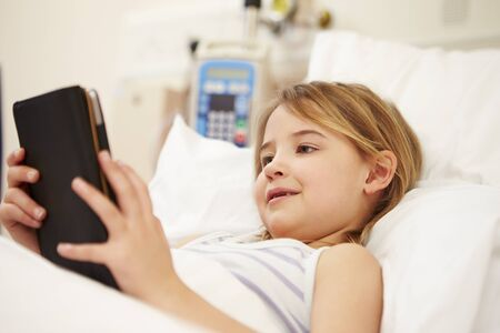 hospital patient: Young Female Patient Using Digital Tablet In Hospital Bed