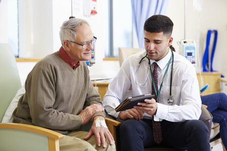 Man Having Chemotherapy With Doctor Using Digital Tablet