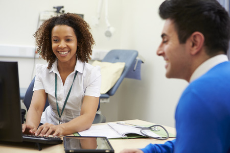 Female Consultant Meeting With Male Patient Stock Photo