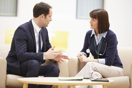 smiling businessman: Businessman Discussing Test Results Female Doctor