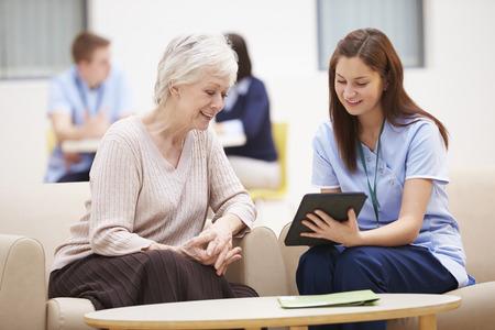 Mujer mayores que discuten los resultados de prueba con la enfermera Foto de archivo