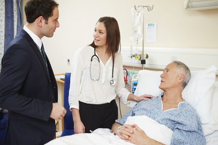 rounds: Medical Staff On Rounds Examining Senior Male Patient
