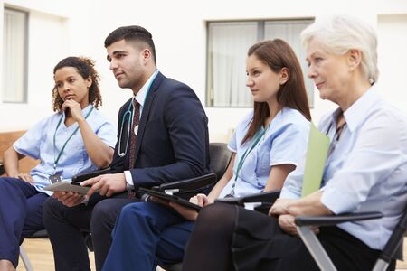 middle eastern clothing: Members Of Medical Staff In Meeting Together Stock Photo