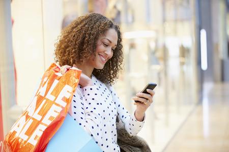 Vrouw in winkelcomplex met behulp van mobiele telefoon Stockfoto
