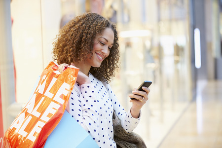 happy shopping: Woman In Shopping Mall Using Mobile Phone