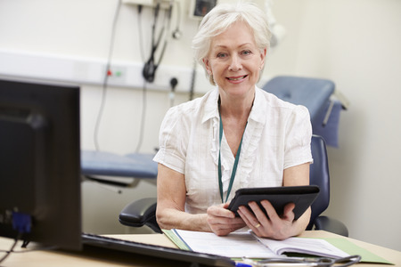senior female: Female Consultant Working At Desk Using Digital Tablet