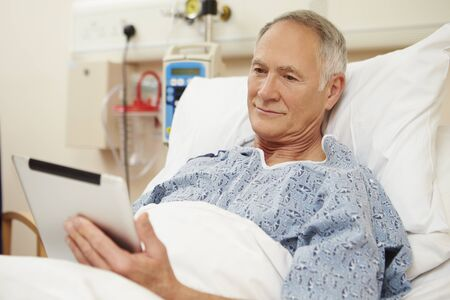 e book reader: Senior Male Patient Using Digital Tablet In Hospital Bed