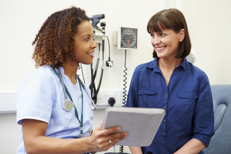 happy patient: Nurse Showing Patient Test Results On Digital Tablet Stock Photo