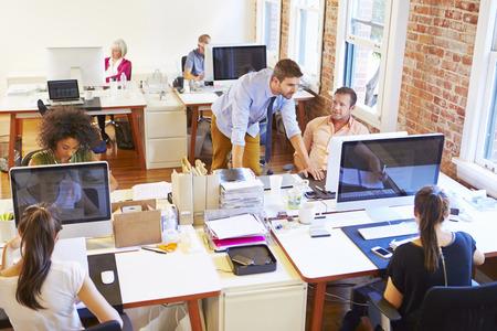 Brede kijkhoek van Busy ontwerp Office Met Arbeiders Bij Bureaus